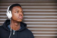 听到在城市布局的音乐的十几岁的男孩 免版税图库摄影