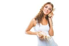 听到在壳的海音乐的美丽的女孩在被隔绝的白色 库存照片