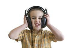 听到在大黑耳机的音乐的小男孩 背景查出的白色 库存照片