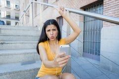 听到在她巧妙的电话的音乐的可爱的拉丁妇女 免版税库存照片