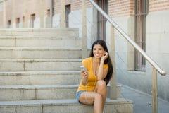 听到在她巧妙的电话的音乐的可爱的拉丁妇女 免版税库存图片