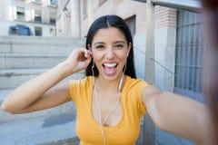 听到在她巧妙的电话的音乐的可爱的拉丁妇女 免版税图库摄影