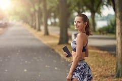 听到在她的手机的音乐的可爱的运动的妇女 免版税库存图片