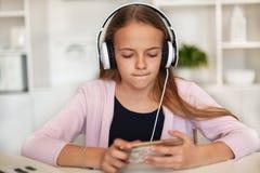 听到在她的电话和耳机的音乐的女孩 库存图片