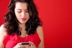 听到在她的电话的音乐的少年 图库摄影