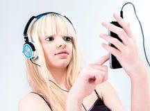 听到在她的smartphone的音乐的可爱的白肤金发的女孩 免版税库存照片