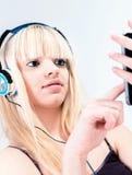 听到在她的smartphone的音乐的可爱的白肤金发的女孩 免版税图库摄影