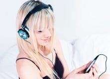 听到在她的smartphone的音乐的逗人喜爱的白肤金发的女孩 免版税库存图片
