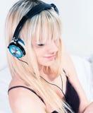 听到在她的smartphone的音乐的逗人喜爱的白肤金发的女孩 库存照片