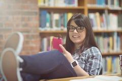 听到在手机的音乐的女学生画象 库存图片