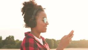 听到在无线耳机和手机佩带的太阳镜的音乐的非裔美国人的混合的族种少年在日落 股票视频