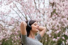 听到在无线耳机的音乐的年轻女人在有樱花树的一个公园 免版税库存照片