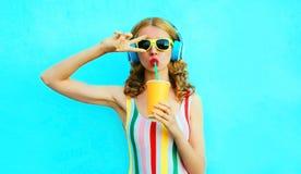 听到在无线耳机的音乐的画象凉快的女孩饮用的果汁在五颜六色的蓝色 免版税库存照片