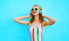 听到在无线耳机的音乐的画象愉快的微笑的妇女在五颜六色的蓝色 库存照片