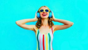 听到在无线耳机的音乐的画象愉快的微笑的妇女在五颜六色的蓝色 库存图片
