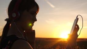 听到在智能手机的音乐的女孩旅客在美好的春天日落的光芒 有耳机的少女和与 股票录像