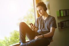 听到在智能手机的音乐的少年 库存图片