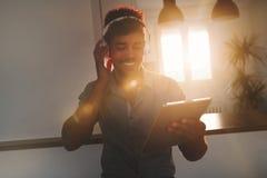 听到在片剂的音乐的英俊的非裔美国人的人 库存图片