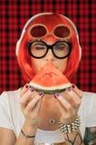 听到在白色耳机的音乐和举行片断成熟的一顶红色假发和玻璃的一个时髦的女人 库存图片