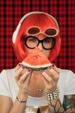 听到在白色耳机的音乐和举行片断成熟的一顶红色假发和玻璃的一个时髦的女人 图库摄影