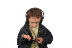 听到在白色背景的音乐的男孩 库存图片