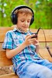 听到在立体声耳机的音乐的愉快的孩子 免版税库存照片