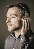 听到在立体声耳机的音乐的年轻人 免版税库存照片