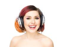 听到在耳机中的音乐的美丽的女孩 免版税库存照片