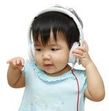听到在耳机和享用的音乐的逗人喜爱的孩子 免版税库存图片