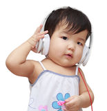 听到在耳机和enjo的音乐的逗人喜爱的孩子 库存图片