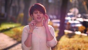 听到在耳机的音乐和跳舞以在秋季公园背景的欢欣的年轻粉发的女孩画象  股票视频