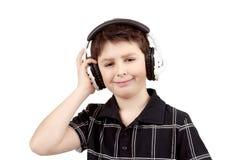 听到在耳机的音乐的一个愉快的微笑的年轻男孩的画象 库存图片