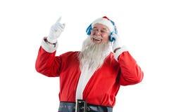 听到在耳机的音乐的圣诞老人 免版税库存照片