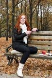 听到在耳机的音乐的少妇在秋天公园 图库摄影