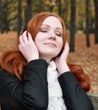 听到在耳机的音乐的少妇在秋天公园 免版税库存图片