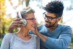 听到在耳机的音乐的年轻混合的族种夫妇 免版税库存图片