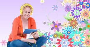 听到在耳机的音乐的微笑的妇女使用片剂个人计算机反对花卉背景 库存图片