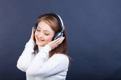 听到在耳机的音乐的微笑的妇女 免版税库存图片