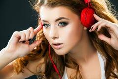 听到在耳机的音乐的性感的少妇跳舞 免版税库存图片