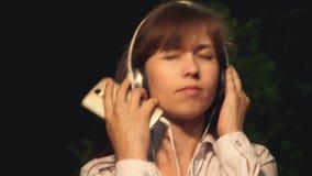 听到在耳机的音乐的愉快的女孩在智能手机 年轻美女跳舞,微笑和享受音乐在 股票录像