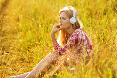 听到在耳机的音乐的愉快的女孩 免版税库存图片