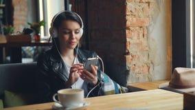 听到在耳机的音乐的愉快的女生使用在咖啡馆的智能手机 股票录像