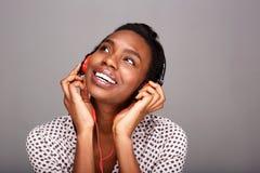 听到在耳机的音乐的愉快的黑人妇女画象  库存图片