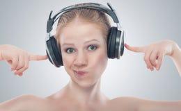 听到在耳机的音乐的滑稽的女孩 免版税库存照片
