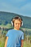 听到在耳机的音乐的男孩本质上 库存图片