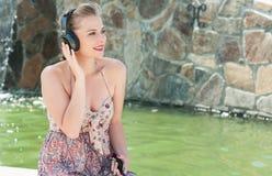 听到在耳机的音乐的美丽的女孩外面 免版税库存照片