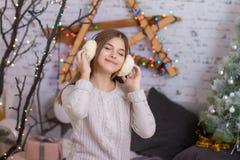 听到在耳机的音乐的美丽的女孩 库存图片
