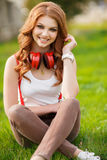 听到在耳机的音乐的美丽的女孩 库存照片