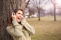 听到在耳机的音乐的美丽的女孩 免版税库存图片