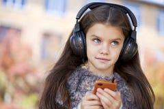 听到在耳机的音乐的美丽的小女孩 免版税库存照片